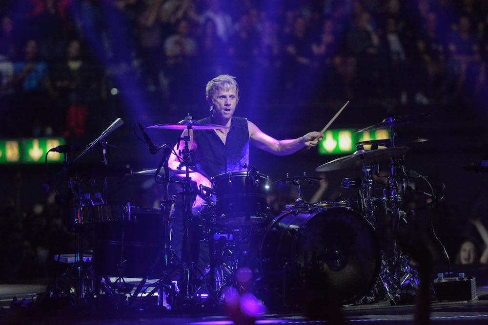Dominic Howard haut auf das Schlagzeug.